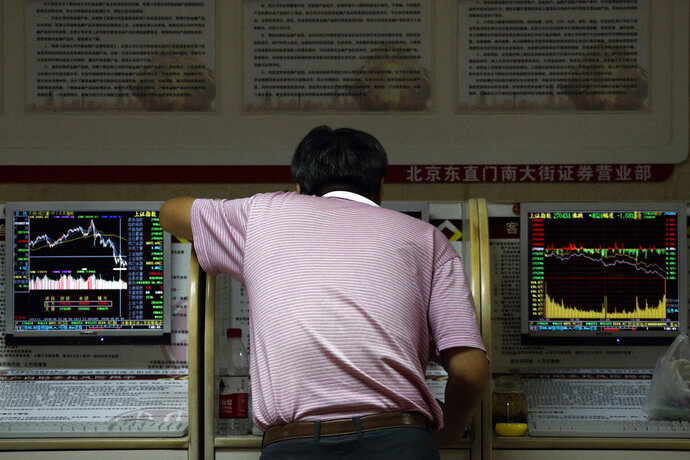An investor checks stock prices at a brokerage house in Beijing, Thursday, Sept. 6, 2018. Asian markets are mixed on fears that the U.S. would soon impose tariffs on another $200 billion of Chinese goods, as public consultations draw to a close. (AP Photo/Andy Wong)