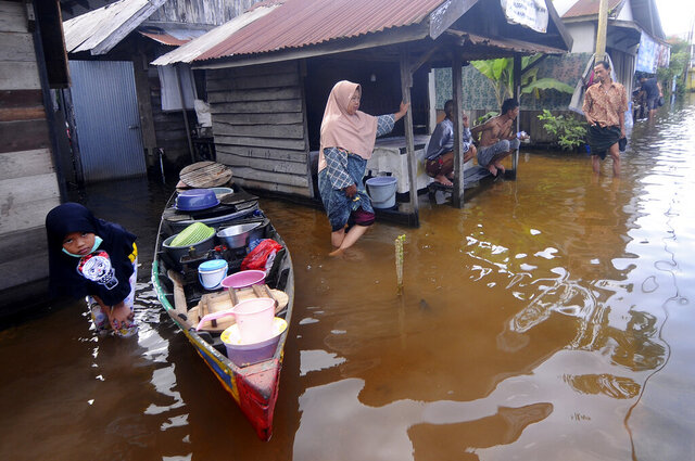 People talk outside their homes at a neighborhood affected by flood in Banjarmasin, South Kalimantan on Borneo Island, Indonesia, Sunday, Jan. 17, 2021.  many thousands of people have been evacuated and a number have been killed in recent days in flooding on Indonesia's Borneo island, officials said Sunday. (AP Photo/Iman Satria)