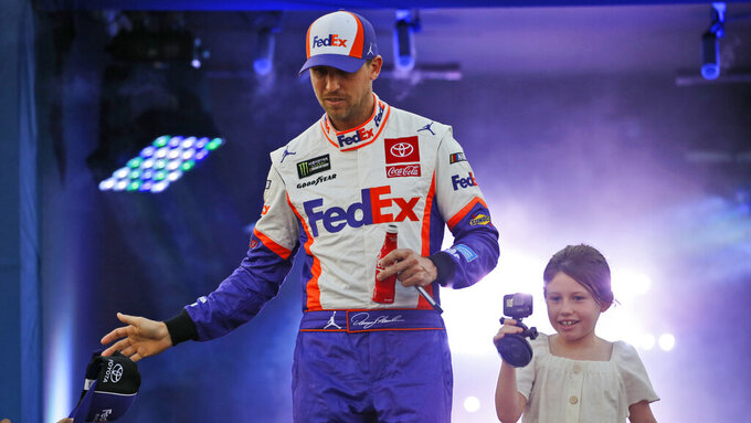 Denny Hamlin and his daughter, Taylor James, greet fans during driver introductions for the NASCAR Monster Energy Cup series auto race at Richmond Raceway in Richmond, Va., Saturday, Sept. 21, 2019. (AP Photo/Steve Helber)