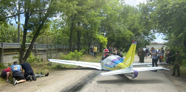 A light airplane crash-lands in Ukraine's southern city of Odesa, Ukraine, Wednesday, June 17, 2020. The plane crash-landed killing one person and injuring another. Local police said the two were the only people on board the plane (Ukrainian Police Press Office via AP)