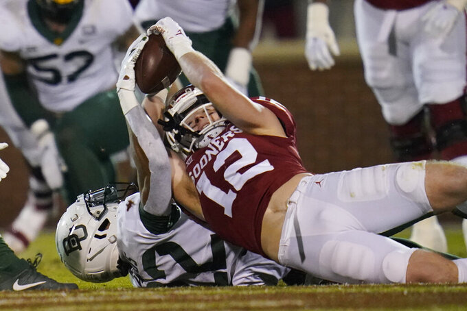 Oklahoma wide receiver Drake Stoops (12) comes down with a pass reception in front of Baylor safety JT Woods (22) in the first half an NCAA college football game Saturday, Dec. 5, 2020, in Norman, Okla. (AP Photo/Sue Ogrocki)