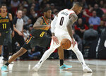 Portland Trail Blazers guard Damian Lillard, right, dribbles around Atlanta Hawks guard Tyrone Wallace during the first half of an NBA basketball game in Portland, Ore., Sunday, Nov. 10, 2019. (AP Photo/Craig Mitchelldyer)