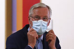 European Commission's Head of Task Force for Relations with the United Kingdom Michel Barnier puts on his protective face mask prior to meeting with European Council President Charles Michel at the EU Council building in Brussels, Friday, Sept. 18, 2020. (Yves Herman, Pool via AP)