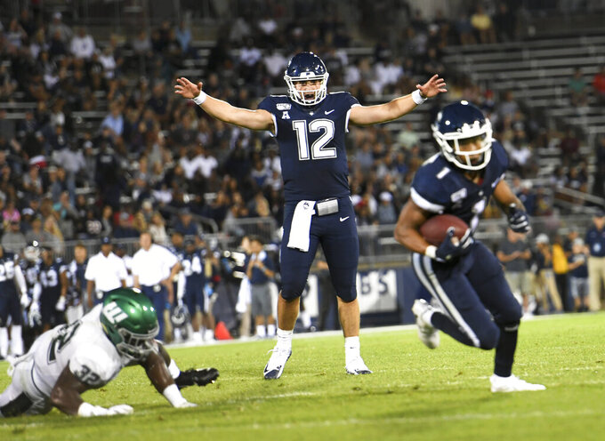 Connecticut quarterback Mike Beaudry (12) watches Connecticut running back Art Thompkins (1) run the ball in for a touchdown during the second half of the team's NCAA college football game against Wagner on Thursday, Aug. 29, 2019, in East Hartford, Conn. (AP Photo/Stephen Dunn)