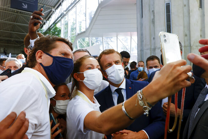 French President Emmanuel Macron takes a selfie, as he arrives to visit the International Catering, Hotel and Food Trade Fair (SIRHA) in Lyon, central France, Monday Sept. 27, 2021.(Denis Balibouse/Pool via AP)