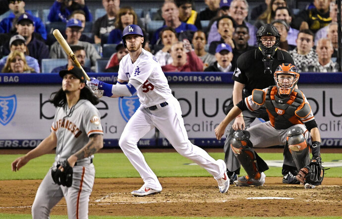 Los Angeles Dodgers' Cody Bellinger watches his two-run home run off San Francisco Giants relief pitcher Dereck Rodriguez, left, during the seventh inning of a baseball game Wednesday, June 19, 2019, in Los Angeles. (AP Photo/Mark J. Terrill)