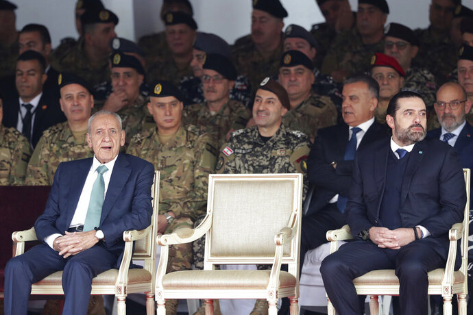 Lebanese Parliament Speaker Nabih Berri, left, and resigned Lebanese Prime Minister Saad Hariri attend a military parade to mark the 76th anniversary of Lebanon's independence from France at the Lebanese Defense Ministry, in Yarzeh near Beirut, Lebanon, Friday, Nov. 22, 2019. Lebanon's top politicians Friday attended a military parade on the country's 76th Independence Day, appearing for the first time since the government resigned amid nationwide protests now in their second month. (AP Photo/Hassan Ammar)