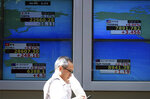 A man walks past an electronic stock board showing Japan's Nikkei 225 index and lather coin try's index at a securities firm in Tokyo Friday, Aug. 10, 2018. Shares were lower in Asia on Friday, tracking losses on Wall Street, despite the release of data showing Japan's economy resumed its longtime expansion in the last quarter. (AP Photo/Eugene Hoshiko)