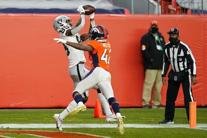 Las Vegas Raiders wide receiver Bryan Edwards (89) catches a pass for a touchdown over Denver Broncos cornerback Parnell Motley during the first half of an NFL football game, Sunday, Jan. 3, 2021, in Denver. (AP Photo/Jack Dempsey)