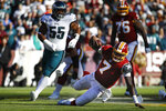 Washington Redskins quarterback Dwayne Haskins (7) looses his footing while running with the ball in the first half of an NFL football game against the Philadelphia Eagles, Sunday, Dec. 15, 2019, in Landover, Md. Giving chase is Philadelphia Eagles defensive end Brandon Graham (55). (AP Photo/Patrick Semansky)