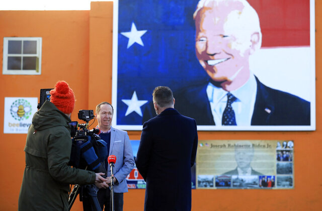 Joe Biden's cousin Joe Blewitt speaks to the media underneath his mural painted on a wall in Ballina, Ireland, Wednesday, Jan. 20, 2021. Joe Biden's great-great grandfather Patrick Blewitt was born in Ballina, County Mayo, in 1832. He left for the US in 1850, aged 18. (AP Photo/Peter Morrison)