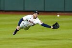 FILE - Inn this July 27, 2020, file photo, Houston Astros center fielder George Springer dives while trying to catch a double by Seattle Mariners' J.P. Crawford during the seventh inning of a baseball game in Houston. (AP Photo/David J. Phillip, File)
