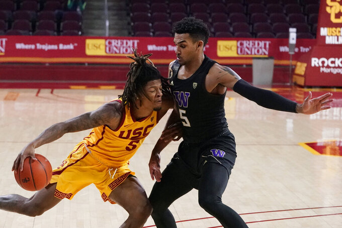 Southern California guard Isaiah White, left, is defended by Washington guard Jamal Bey during the second half of an NCAA college basketball game Thursday, Jan. 14, 2021, in Los Angeles. (AP Photo/Marcio Jose Sanchez)