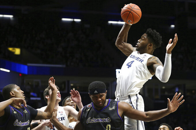 Xavier forward Tyrique Jones (4) rebounds the ball during the first half of an NCAA college basketball game against Western Carolina, Wednesday, Dec. 18, 2019 in Cincinnati. (Kareem Elgazzar/The Cincinnati Enquirer via AP)