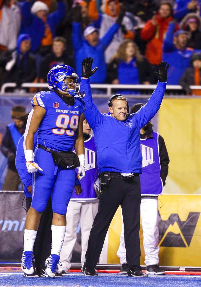 Boise State head coach Bryan Harsin and Boise State linebacker Curtis Weaver (99) celebrate a touchdown in the final seconds against Utah State in an NCAA college football game, Saturday, Nov. 24, 2018, in Boise, Idaho. Boise State won 33-24. (AP Photo/Steve Conner)