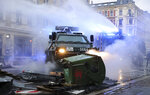 """A water cannon and an evacuation tank clear a barricade on Wolfgang-Heinze-Strasse after riots broke out at the end of a left-wing demonstration, in Leipzig, Germany, Saturday, Sept. 18, 2021. The campaign alliance """"We are all Linx"""" had mobilized nationwide for the demonstration. (Jan Woitas/dpa via AP)"""
