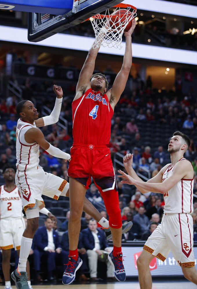 Arizona's Chase Jeter, center, attempts a dunk over Southern California's Shaqquan Aaron, left, and Southern California's Nick Rakocevic, right, during the second half of an NCAA college basketball game in the first round of the Pac-12 men's tournament Wednesday, March 13, 2019, in Las Vegas. (AP Photo/John Locher)