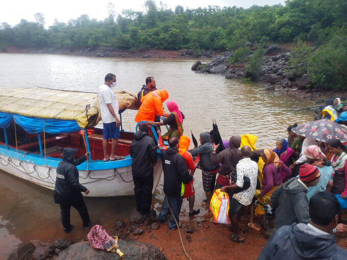 This photograph provided by India's National Disaster Response Force (NDRF) shows NDRF personnel rescuing stranded people in Satara, in the western Indian state of Maharashtra, Friday, July 23, 2021. Landslides triggered by heavy monsoon rains hit parts of western India, killing more than 30 people and leading to the overnight rescue of more than 1,000 other people trapped by floodwaters, officials said Friday.(National Disaster Response Force via AP)