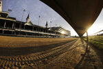 FILE - In this May 7, 2020 file photo the sun rises over the track at Churchill Downs in Louisville, Ky. Horse racing is in a state of transition at a time usually reserved for Triple Crown season. The Preakness would have been run Saturday, May 16, 2020 in Baltimore. But Pimlico Race Course and many tracks across North America remain dark because of the coronavirus pandemic. There is some light at the end of the tunnel as tracks including Churchill Downs in Kentucky are getting back to live racing without fans. (AP Photo/Darron Cummings, file)