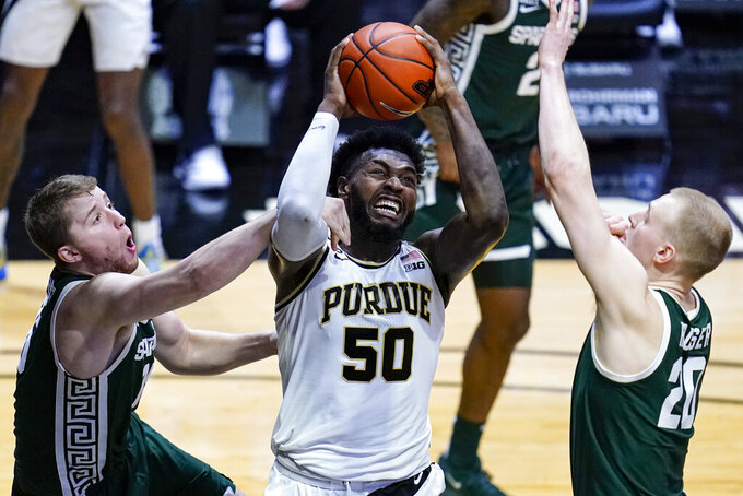 Purdue forward Trevion Williams (50) is fouled by Michigan State forward Thomas Kithier (15) as he shoots next to Michigan State forward Joey Hauser (20) during the second half of an NCAA college basketball game in West Lafayette, Ind., Tuesday, Feb. 16, 2021. Purdue won 75-65.(AP Photo/Michael Conroy)