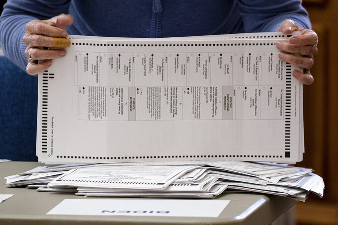 FILE - Officials sort ballots during an audit at the Floyd County administration building in Rome, Ga. on Friday morning, Nov. 13, 2020.  On Friday, Nov. 20, The Associated Press reported on stories circulating online incorrectly asserting that the identities of deceased residents in Georgia were used to illegally cast ballots in the 2020 presidential election. (AP Photo/Ben Gray, File)