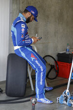 Monster Energy NASCAR Cup Series driver Bubba Wallace looks at his phone before practice for the NASCAR Brickyard 400 auto race at the Indianapolis Motor Speedway, Saturday, Sept. 7, 2019 in Indianapolis. (AP Photo/Darron Cummings)