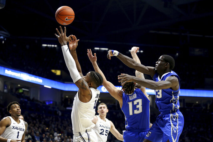 Xavier forward Tyrique Jones (4) secures a rebound away from Creighton forward Christian Bishop (13) in the first half of an NCAA college basketball game Saturday, Jan. 11, 2020, in Cincinnati. (Kareem Elgazzar/The Cincinnati Enquirer via AP)