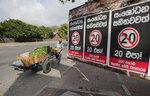 A Sri Lankan vegetable seller pushes his cart past posters against a proposed constitutional amendment that would consolidate power in the president's hands in Colombo, Sri Lanka, Tuesday, Oct. 20, 2020. Sinhalese reads