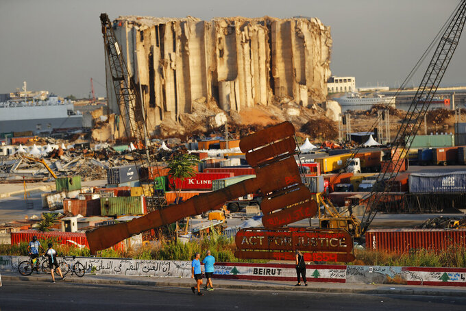 People pass next of a justice symbol monument that sits in front of towering grain silos gutted in the massive August 2020 explosion at the Beirut port that claimed the lives of more than 200 people, in Beirut, Lebanon, Wednesday, Aug. 4, 2021. A year after the deadly blast, families of the victims are consumed with winning justice for their loved ones and punishing Lebanon's political elite, blamed for causing the disaster through their corruption and neglect. (AP Photo/Hussein Malla)