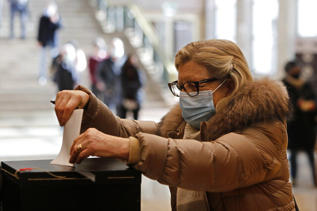 A woman casts her ballot at a polling station in Lisbon, Sunday, Jan. 24, 2021. Portugal holds a presidential election Sunday, choosing a head of state to serve a five-year term. (AP Photo/Armando Franca)