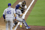 San Diego Padres' Fernando Tatis Jr., right, collides with Los Angeles Dodgers catcher Will Smith, center, as he is tagged out attempting to score from third base on a line out by Manny Machado during the seventh inning of a baseball game Monday, Aug. 3, 2020, in San Diego. Los Angeles Dodgers first baseman Matt Beaty (45) looks on at left. (AP Photo/Gregory Bull)