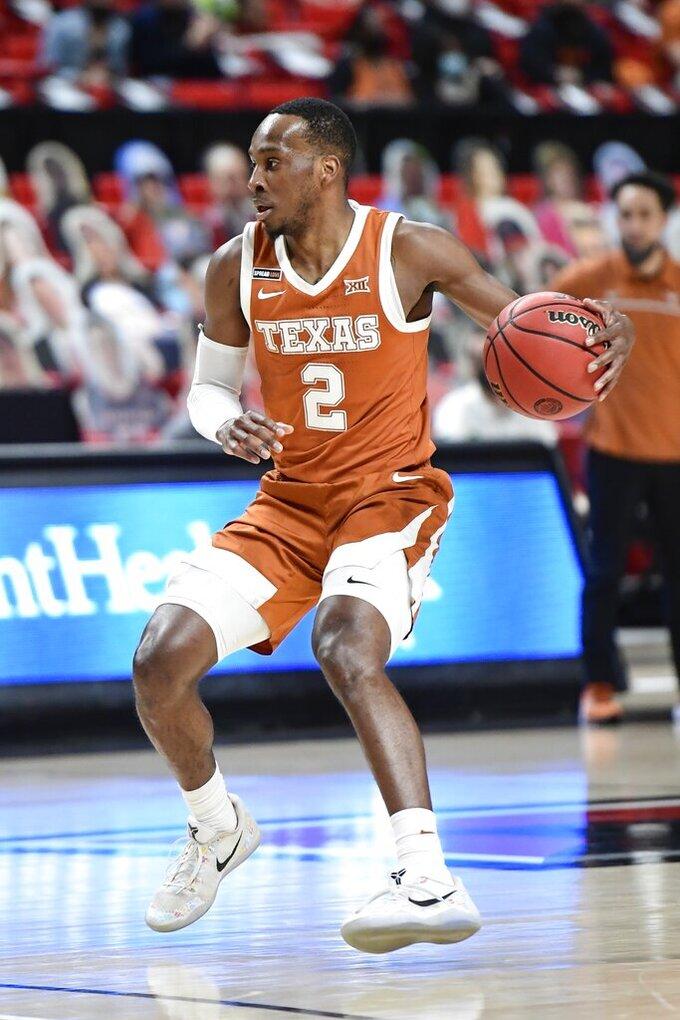 Texas' Matt Coleman III (2) controls the ball during the first half of an NCAA college basketball game against Texas Tech in Lubbock, Texas, Saturday, Feb. 27, 2021. (AP Photo/Justin Rex)