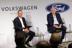 Ford CEO Jim Hackett, right, and Volkswagen CEO Herbert Diess participate in a news conference in New York, Friday, July 12, 2019. Volkswagen will sink $2.6 billion into a Pittsburgh autonomous vehicle company that's mostly owned by Ford as part of a broader partnership on electric and self-driving vehicles, the companies confirmed Friday.  (AP Photo/Seth Wenig)