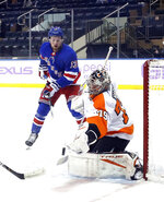 Philadelphia Flyers' Carter Hart (79) makes a save as New York Rangers' Alexis Lafreniere (13) looks for a rebound during an NHL hockey game at Madison Square Garden, Monday, March 15, 2021, in New York. (Bruce Bennett/Pool Photo via AP)