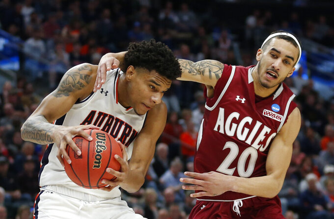 Auburn forward Chuma Okeke, left, pulls down a rebound as New Mexico State guard Trevelin Queen (20) defends in the second half during a first round men's college basketball game in the NCAA Tournament, Thursday, March 21, 2019, in Salt Lake City. (AP Photo/Rick Bowmer)