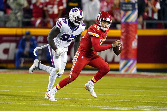 Kansas City Chiefs quarterback Patrick Mahomes (15) scrambles past Buffalo Bills defensive end Mario Addison (97) during the first half of an NFL football game Sunday, Oct. 10, 2021, in Kansas City, Mo. (AP Photo/Charlie Riedel)