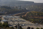 FILE - In this Sunday, Nov. 29, 2020. file photo, roadworks expand a road to Israeli settlements inside the West Bank, near the city of Bethlehem. Israel's premier human rights group has begun describing both Israel and its control of the Palestinian territories as a single