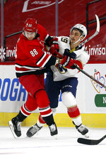 Carolina Hurricanes' Martin Necas (88) collides with Florida Panthers' Mason Marchment (19) during the first period of an NHL hockey game in Raleigh, N.C., Sunday, March 7, 2021. (AP Photo/Karl B DeBlaker)