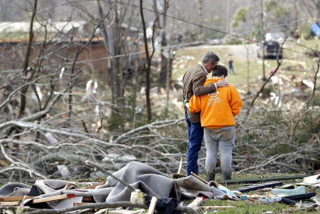 Tennessee Gov. Bill Lee, left, prays with Kayla Cowen, right, as Cowen looks through rubble in hopes of finding a neighbor Tuesday, March 3, 2020, near Cookeville, Tenn. Lee was touring damaged areas and met Cowen as she was searching. Tornadoes ripped across Tennessee early Tuesday, shredding buildings and burying people in piles of rubble and wrecked basements. (AP Photo/Mark Humphrey)