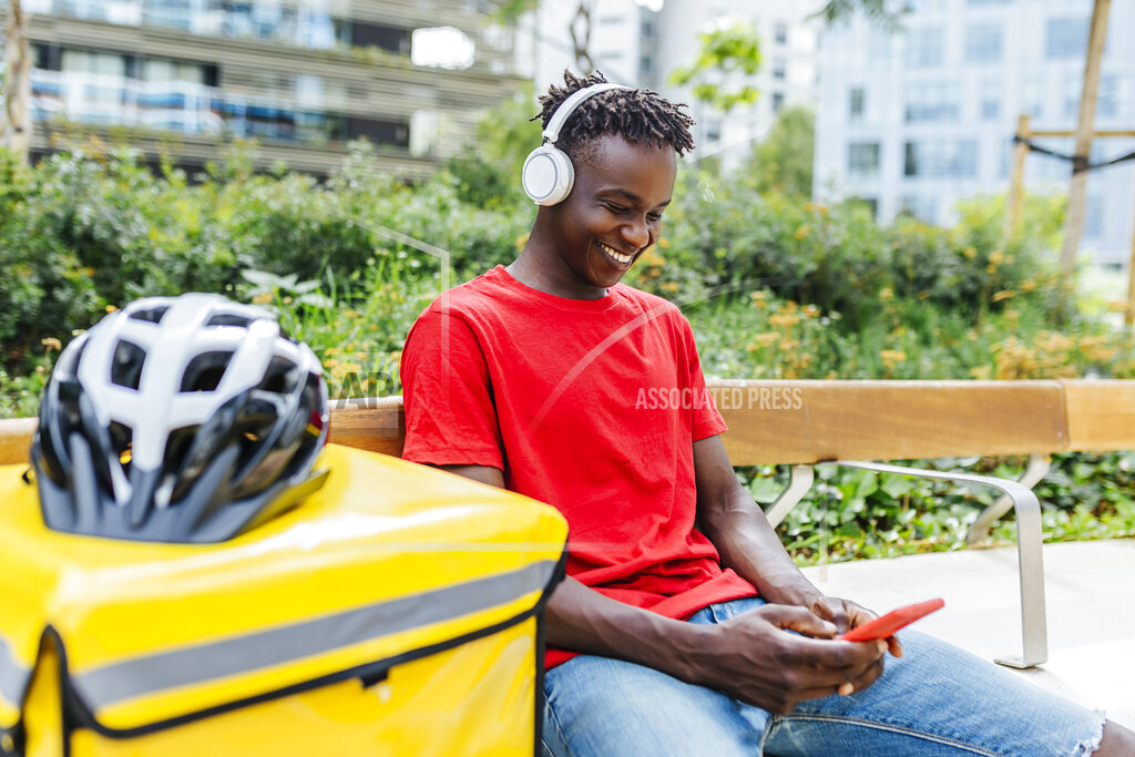 Smiling delivery man using mobile phone while listening music through wireless headphones on bench