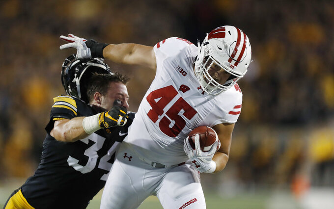 FILE - In this Saturday, Sept. 22, 2018, file photo, Wisconsin fullback Alec Ingold (45) runs the ball as he pushes off the helmet of Iowa linebacker Kristian Welch (34) during the first half of an NCAA college football game, in Iowa City. The Badgers have a chance to grab the lead in the crowded Big Ten West and take a key step toward their third straight appearance in the conference championship game when they visit Northwestern on Saturday, Oct. 27. (AP Photo/Matthew Putney, File)
