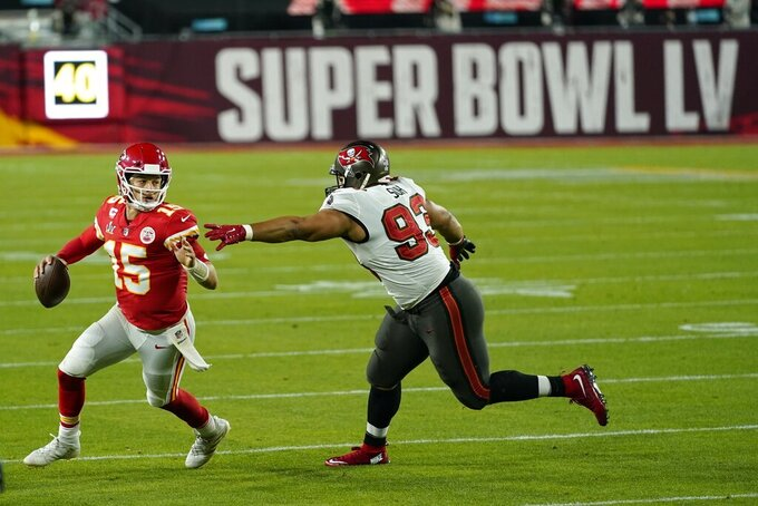 Tampa Bay Buccaneers defensive end Ndamukong Suh tries to tackle Kansas City Chiefs quarterback Patrick Mahomes during the second half of the NFL Super Bowl 55 football game Sunday, Feb. 7, 2021, in Tampa, Fla. (AP Photo/Mark Humphrey)