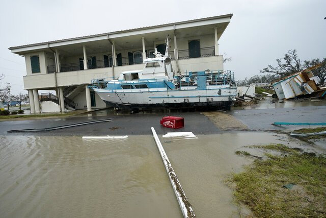 Flooding surrounds a damaged building and boat Friday, Aug. 28, 2020, in Cameron, La., after Hurricane Laura moved through the area Thursday. (AP Photo/David J. Phillip)