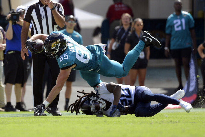 Jacksonville Jaguars tight end Dan Arnold (85) dives over Tennessee Titans cornerback Jackrabbit Jenkins for extra yardage after a reception during the first half of an NFL football game, Sunday, Oct. 10, 2021, in Jacksonville, Fla. (AP Photo/Phelan M. Ebenhack)
