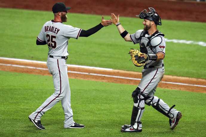 Arizona Diamondbacks relief pitcher Archie Bradley, left and catcher Stephen Vogt celebrate the 4-1 win over the Texas Rangers in a baseball game Tuesday, July 28, 2020, in Arlington, Texas. (AP Photo/Richard W. Rodriguez)