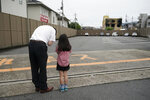 A man and his daughter pray for the victims of Thursday's fire at the Kyoto Animation Studio building, background right, Saturday, July 20, 2019, in Kyoto, Japan. The man suspected of setting ablaze a beloved Japanese animation studio was raging about theft and witnesses and media reported he had a grudge against the company, as questions arose why such mass killings keep happening in the country. (AP Photo/Jae C. Hong)