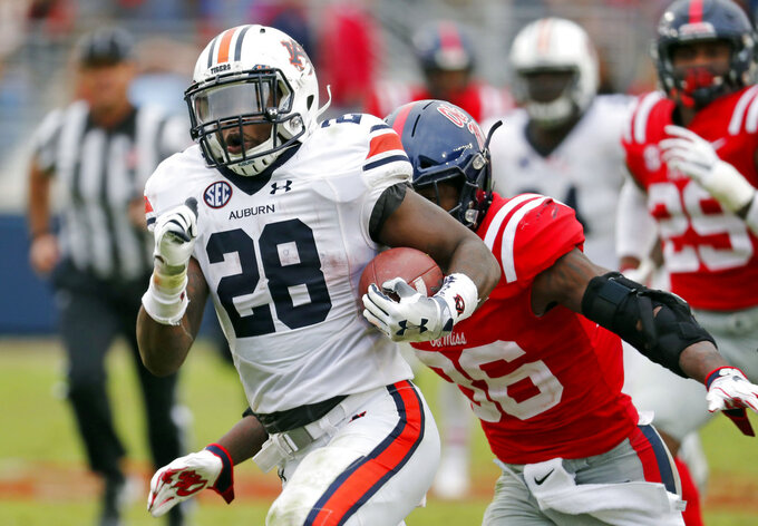 Auburn running back JaTarvious Whitlow (28) runs past Mississippi defenders towards the goal line, before fumbling the ball into the end zone, during the second half of an NCAA college football game on Saturday, Oct. 20, 2018, in Oxford, Miss. Auburn recovered the fumble for a touchdown and won 31-16. (AP Photo/Rogelio V. Solis)