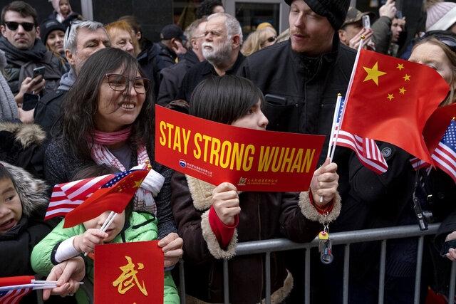 A paradegoer holds a sign of support for Wuhan, China, at the center of the coronavirus outbreak, as participants in the Lunar New Year parade pass by in the Chinatown neighborhood of New York, Sunday, Feb. 9, 2020. (AP Photo/Craig Ruttle)
