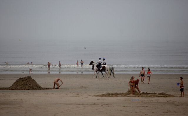 Police patrol the beach on horseback at the Belgian seaside resort of Blankenberge, Belgium, Tuesday, Aug. 11, 2020. A skirmish took place on the beach on Saturday, Aug. 8, 2020 which resulted in two coastal communities banning day trippers from the city. (AP Photo/Virginia Mayo)