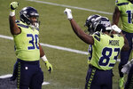 Seattle Seahawks running back Carlos Hyde (30) celebrates with teammates, including wide receiver David Moore (83) after Hyde scored a touchdown against the Arizona Cardinals during the second half of an NFL football game, Thursday, Nov. 19, 2020, in Seattle. (AP Photo/Elaine Thompson)